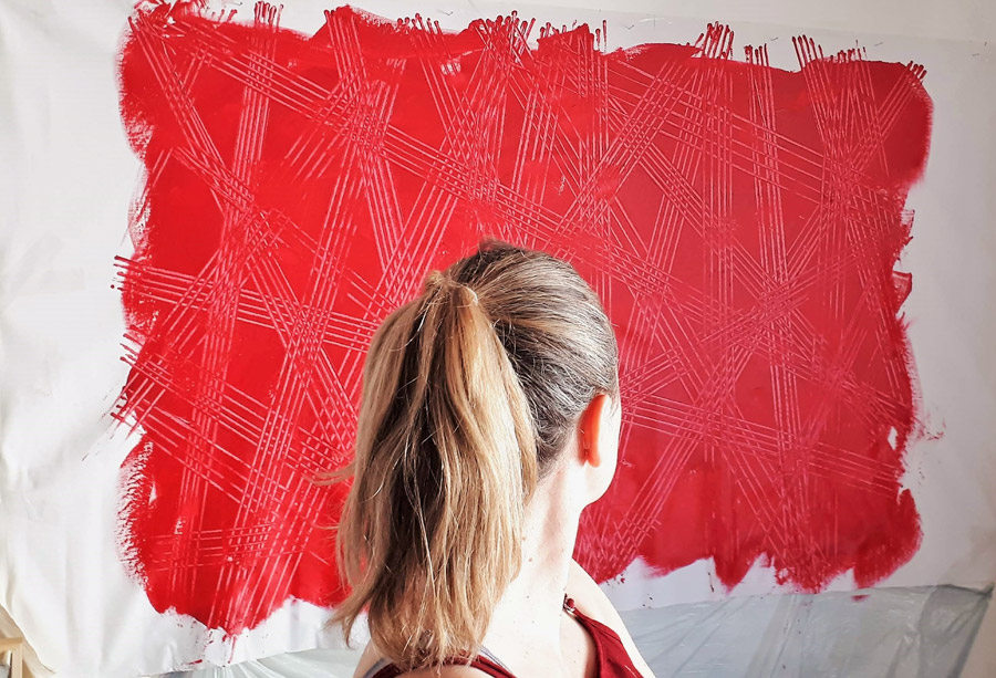 Artist Paraskevi in front of a red artwork